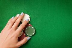 La mano de la mujer que sostenía las fichas de póker en casino verde sentía el fondo imágenes de archivo libres de regalías