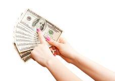La mano de la mujer que sostiene 100 billetes de banco del dólar de EE. UU. Fotos de archivo libres de regalías