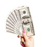 La mano de la mujer que sostiene 100 billetes de banco del dólar de EE. UU. Imágenes de archivo libres de regalías