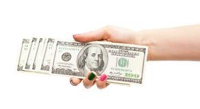 La mano de la mujer que sostiene 100 billetes de banco del dólar de EE. UU. Imagen de archivo