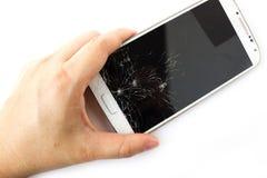 La mano de la mujer que sostiene el teléfono elegante blanco roto fotografía de archivo libre de regalías
