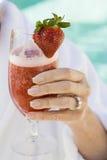 La mano de la mujer que sostiene el vidrio de jugo de la fresa fotografía de archivo libre de regalías