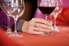 La mano de la mujer que sostiene la copa de vino en la tabla del restaurante Fotos de archivo