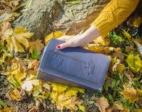 La mano de la mujer que sostiene un libro con amarillo se va en un fondo Fotografía de archivo libre de regalías