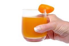 La mano de la mujer que sostiene un vidrio de jugo del albaricoque Fotos de archivo