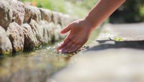 La mano de la mujer que sumerge en el agua Fotos de archivo libres de regalías
