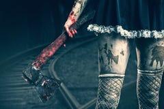 La mano de la mujer sucia que sostiene un hacha sangrienta Imágenes de archivo libres de regalías