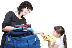 La mano de la mujer y de la hija abarrotó por completo de ropa y del bolso Fotografía de archivo
