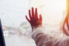 La mano de la niña que mira fuera de la ventana con la llamarada ligera y la lluvia caen sobre el vidrio de la puerta de coche, a Foto de archivo libre de regalías