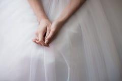 La mano de la novia en el vestido blanco, alista para la ceremonia de boda Foto de archivo