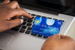 La mano de la persona usando tarjeta de débito mientras que hace compras en línea fotos de archivo libres de regalías