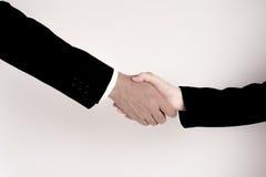 La mano de la sacudida del hombre de negocios con la mujer de negocios en el fondo blanco Concepto de la coordinación imagen de archivo