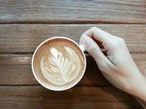 La mano de la señora que sostiene un latte del café en la tabla de madera Imagen de archivo