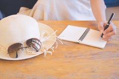 La mano de las mujeres del inconformista en los vestidos poner crema está escribiendo en la libreta con una pluma fotos de archivo