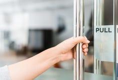 La mano de las mujeres del primer abre el botón de puerta imagen de archivo