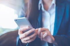 La mano de las mujeres de negocios está utilizando los teléfonos celulares en oficina fotos de archivo