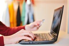 La mano de las mujeres que sostiene la tarjeta del crédito en blanco sobre el ordenador portátil: Compras en línea fotografía de archivo libre de regalías
