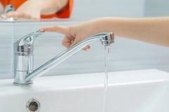 La mano de los childs cierra el agua del mezclador presionando el finger en la manija imagen de archivo