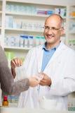 La mano de los clientes que paga el dinero al farmacéutico de sexo masculino For Medicine Foto de archivo