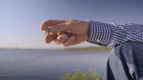 La mano de los hombres del primer sostiene los pequeños guijarros, después los lanza en el agua almacen de metraje de vídeo