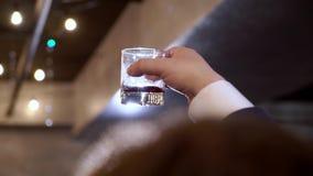 La mano de los hombres que sostiene la copa de vino en festivo metrajes