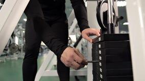 La mano de los hombres reduce el peso en el simulador, pila selecta del peso de la placa del cambio del perno Deporte almacen de metraje de vídeo