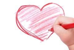 La mano de los niños con el lápiz drena el corazón Imagenes de archivo