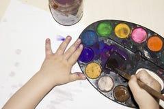 La mano de los niños en la opinión superior de la pintura Imagen de archivo