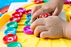 La mano de los niños para jugar a los juegos del alfabeto, foco selectivo al alfabeto Fotografía de archivo libre de regalías
