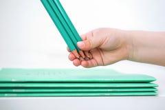 La mano de los niños sostiene los lápices cerca del cuaderno de la escuela foto de archivo