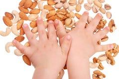 La mano de los niños sostiene tuercas Imágenes de archivo libres de regalías