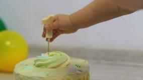 La mano de los niños tira de una vela con el número 1 de la torta metrajes