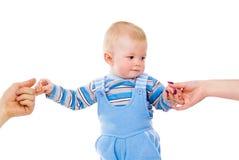 La mano de los padres detiene a un pequeño niño imagenes de archivo