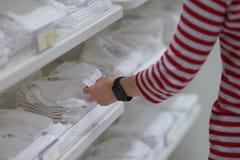 La mano de la mamá elige el traje del bebé en tienda imagen de archivo