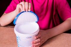 La mano de la muchacha abre una poder de pintura acrílica blanca foto de archivo