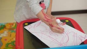 La mano de la muchacha dibuja a un marcador en el papel