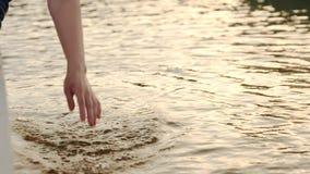 La mano de la muchacha en el agua de la fuente, ella juega en el agua y hace salpica metrajes