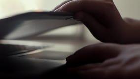 La mano de la mujer abre la tapa de un cierre del ordenador portátil cerca de la ventana en la cámara lenta almacen de metraje de vídeo