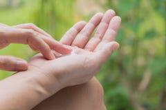 La mano de la mujer aplica la loción en la piel de la mano Fotos de archivo