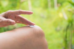 La mano de la mujer aplica la loción en la piel de la rodilla Fotos de archivo libres de regalías