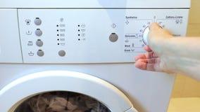La mano de la mujer cierra un macine y un interruptor que se lavan en un programa que se lava y empuja un botón en un panel de de almacen de metraje de vídeo