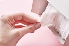 La mano de la mujer coge un coj?n sanitario de la caja, cierre fotos de archivo