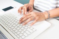 La mano de la mujer con el anillo de bodas usando el ordenador portátil Tecnología y forma de vida foto de archivo libre de regalías