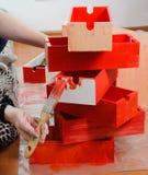 La mano de la mujer con el cepillo comenzar a pintar la caja de madera roja en la pila de cajas rojas imágenes de archivo libres de regalías