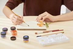 la mano de la mujer con el dibujo de cepillo en la libreta Proceso de la creaci?n de la pintura de la acuarela imágenes de archivo libres de regalías