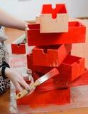 La mano de la mujer con el final de cepillo pintado en caja de madera roja en la pila de cajas rojas imagen de archivo libre de regalías