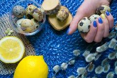 La mano de la mujer con la manicura de Pascua, decoración del día de fiesta, limón, encendido Imagenes de archivo