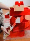 La mano de la mujer con la media pintura del cepillo en caja de madera roja en la pila de cajas rojas imagen de archivo
