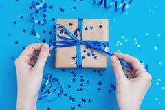 La mano de la mujer at? el arco en la caja de regalo fotografía de archivo libre de regalías