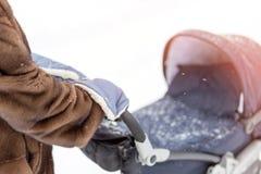 La mano de la mujer en manoplas calientes de una zalea Fotos de archivo
